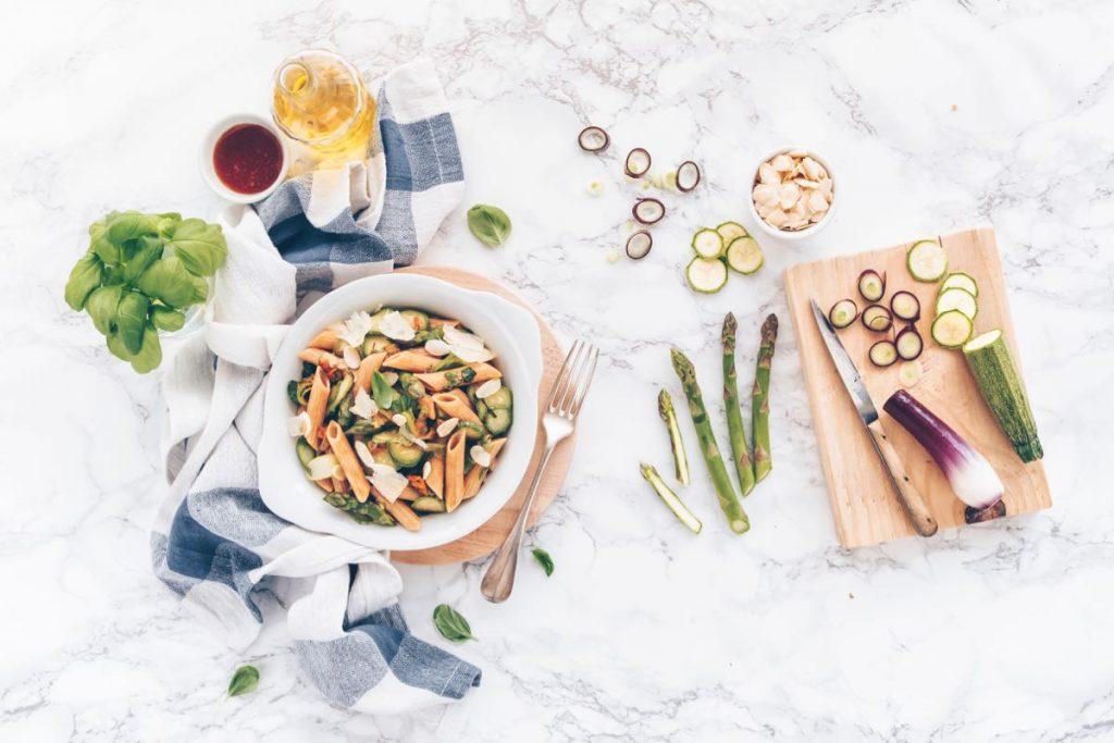 Piatto di penne lenticchie, farro, quinoa, zucchine e miele